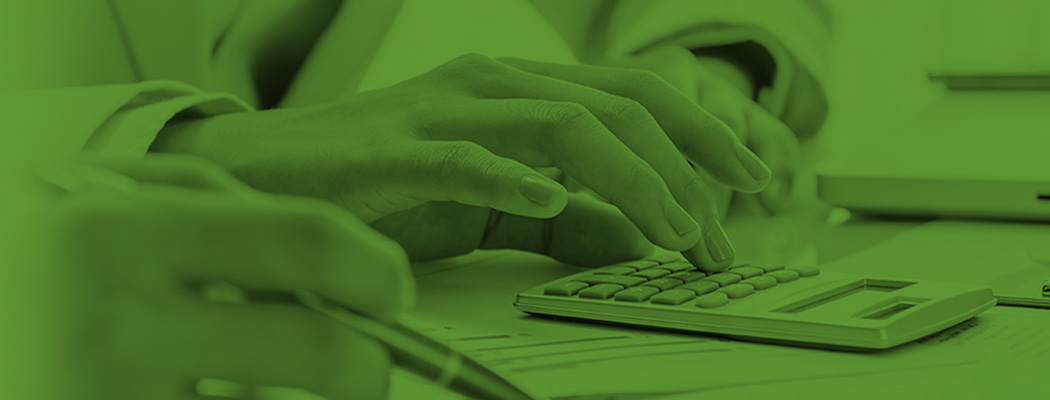 A hand typing on a calculator on with a green overlay on PPC Loan's services page
